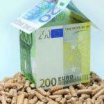 Ein Haufen mit Holzpellets. Darauf Geldscheine, die zu einem Haus gefaltet sind.