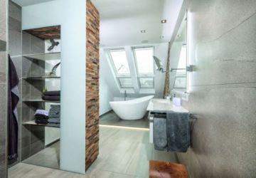 Modernes Badezimmer mit runder Badewanne unter einer schrägen Wand (Badsanierung).