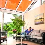 Eine Frau sitzt in einem modernen Wintergarten mit großen Fenstern und einem Dach aus Glas (Wohlfühlklima).