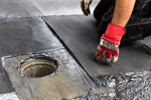 Ein Handwerker repariert eine undichte Stelle auf einem Flachdach