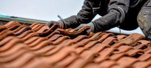 Ein Handwerker entfernt einen defekten Dachziegel.