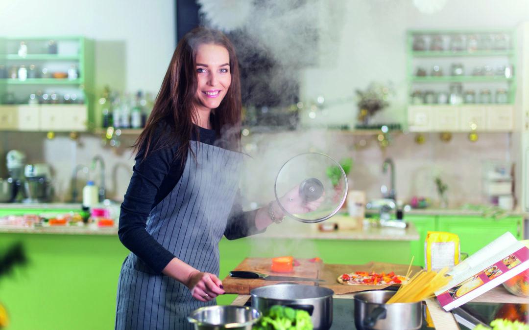 Eine Frau kocht und es entwickelt sich eine Menge Dampf (Ablufthaube).