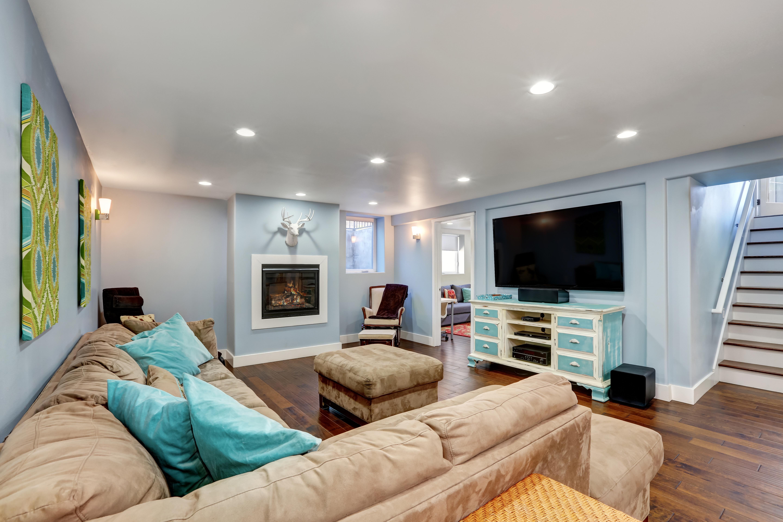 Neubau mit Keller: Kellerraum als Wohnzimmer mit Couch, Fernseher und Kamin