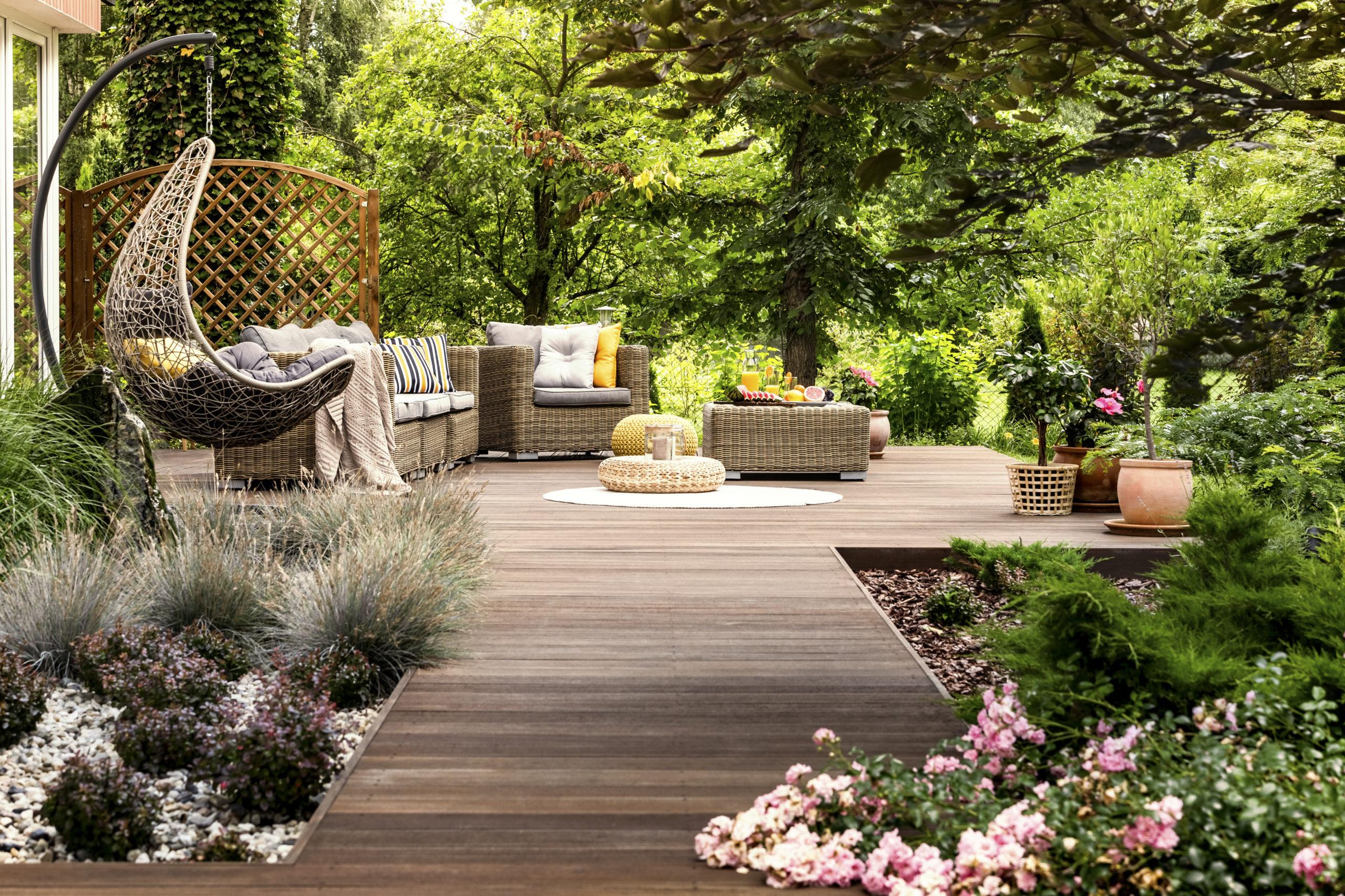Ökologisch bauen: eine Terrasse aus Holz, umgeben von vielen bunten Blumen und grünen Bäumen.