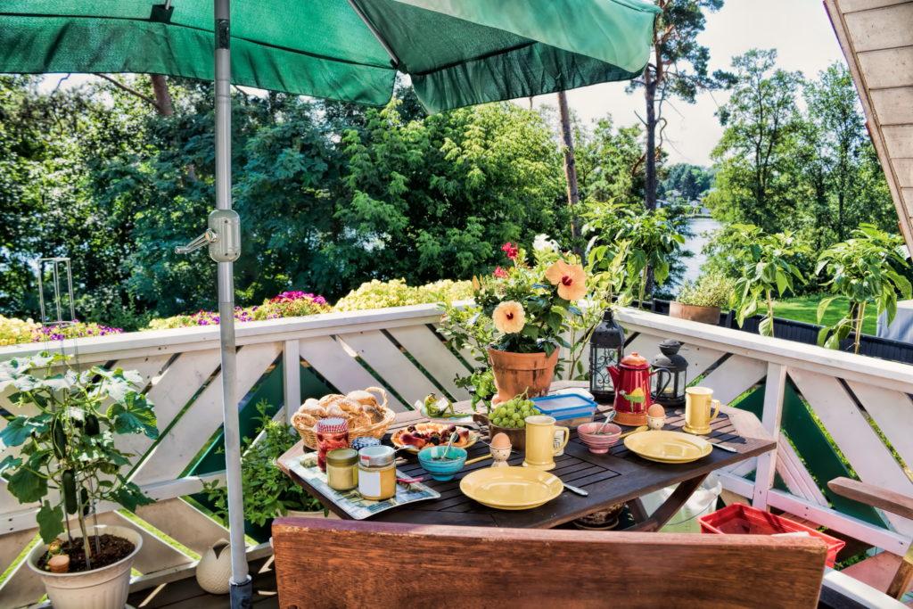 Ein Balkon mit vielen bunten Blumen. Ein Holztisch ist mit Geschirr und Lebensmitteln gedeckt (ökologisch bauen).