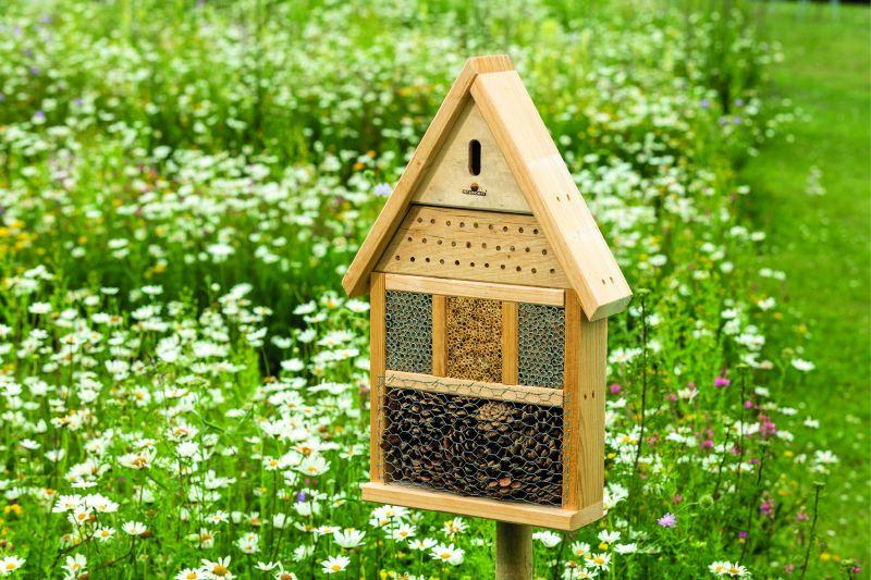 Ökologisch Bauen: ein Insektenhotel steht auf einer grünen Wiese, zwischen vielen Blumen.