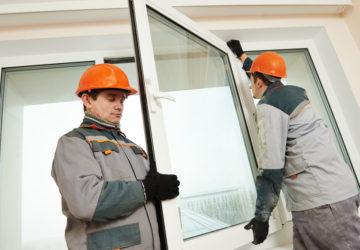 Förderung für Fensteraustausch: zwei männliche Fachkräfte montieren ein großes neues Fenster.